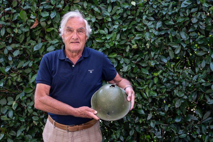 Hans Smulders uit Mook met de helm van zijn vader Jack Smulders uit WOII. In de helm zijn duidelijk de kogelgaten te zien.