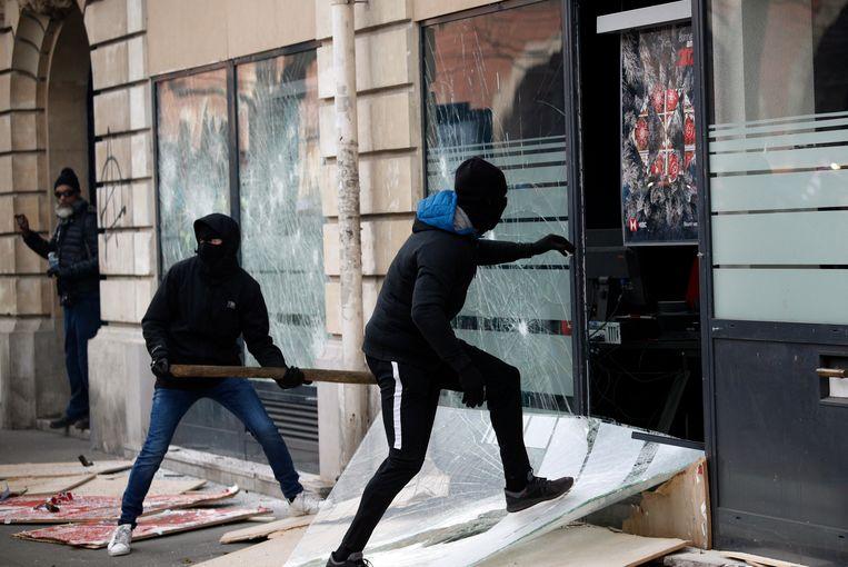 Demonstranten in Paris vernielen ramen tijdens het protest tegen de pensioenplannen van de Franse regering.