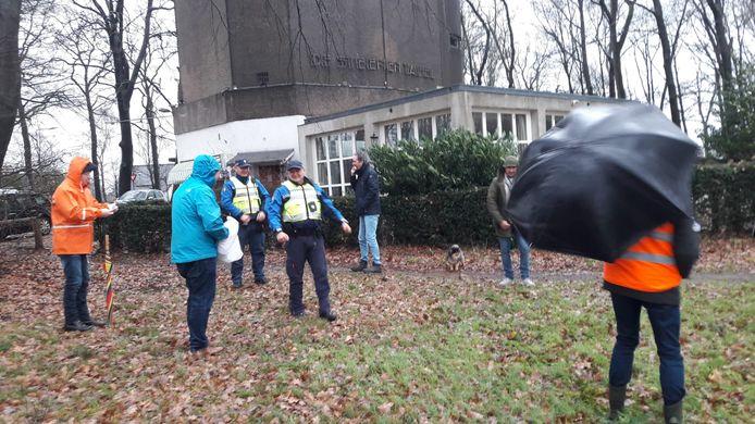 Vrolijk onderonsje tussen twee BOA's en de deelnemers aan de  'bomenwake' bij park Klarenbeek in Arnhem. Actieleider Mark Bosch houdt met moeite zijn paraplu in bedwang bij de onstuimige wind van storm 'Bella'.