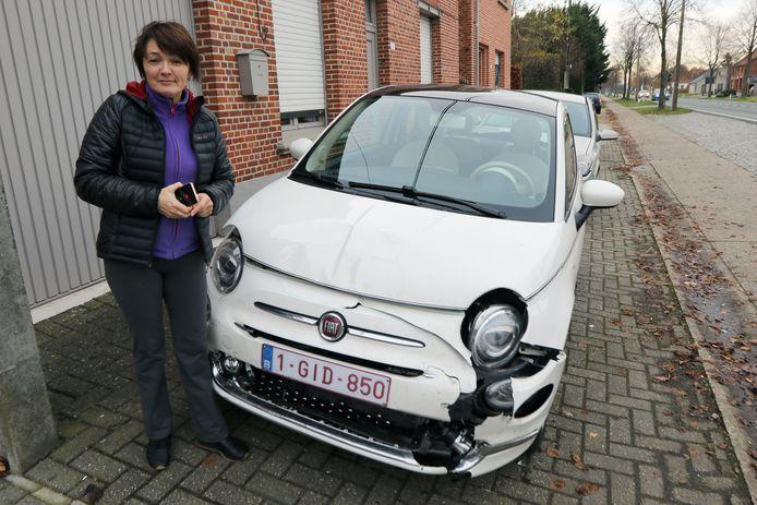 Larysa bij haar beschadigde wagen.