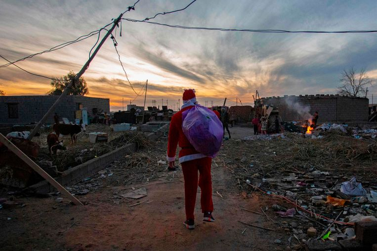 Een inwoner van de Iraakse stad Basra nam zaterdag de rol van kerstman op zich en ging  speelgoed uitdelen aan de kinderen die leven in de puinhopen van de door de oorlog zwaar getroffen buurt.   Beeld AFP
