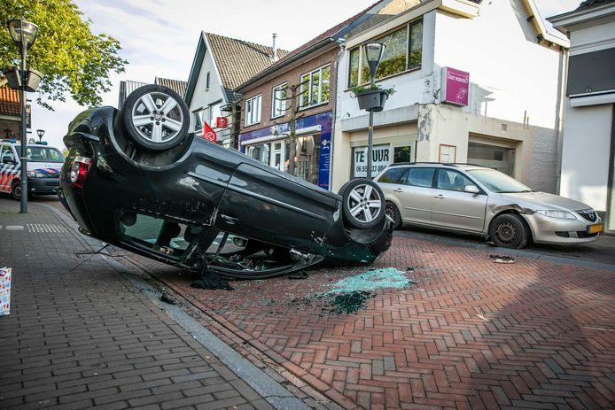 De auto ligt op de kop op straat in Rheden.