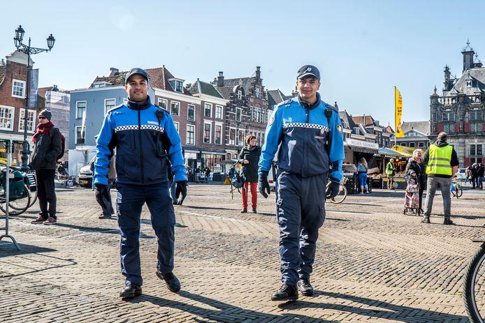 Delftse BOA's aan het werk op de Delfts Markt, toen de coronamaatregelen net waren ingevoerd.