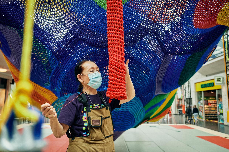 Toshiko Horiuchi MacAdam is bezig aan haar felgekleurde haakwerk in het Kortrijkse winkelcentrum K. Beeld Thomas Sweertvaegher
