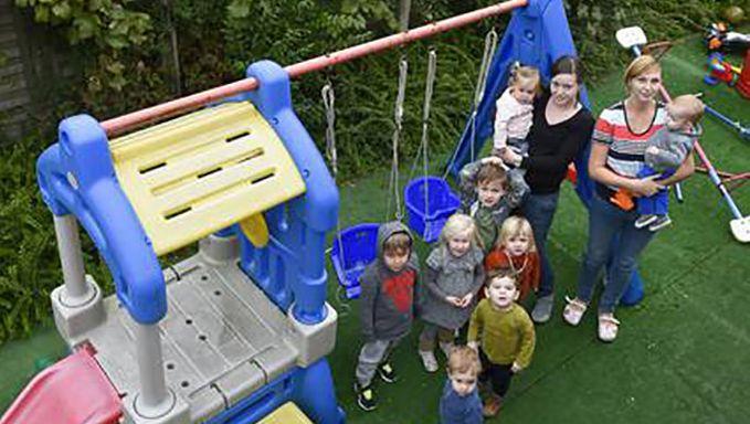Twee medewerkers van Cococinelle samen met enkele kindjes in de tuin aan het speeltuig dicht bij de houten afscheiding.