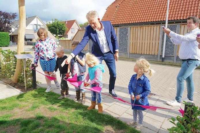 Wethouder Erik Volmerink opent de speeltuin en krijgt voldoende assistentie om het lint door te knippen.