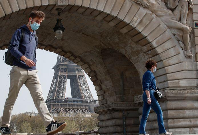 Mensen met mondmasker aan de Eiffeltoren in Parijs