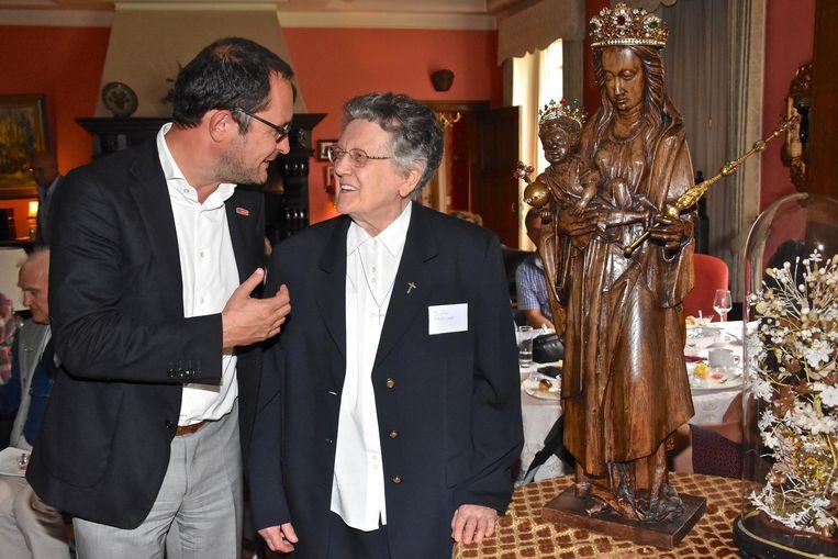 Zuster Angeline overhandigt burgemeester Van Quickenborne met plezier het beeld van O.L.Vrouw ten Putte.