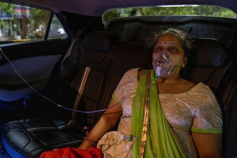 Een vrouw krijgt zuurstof toegediend in een auto, in Ghaziabad. Beeld REUTERS