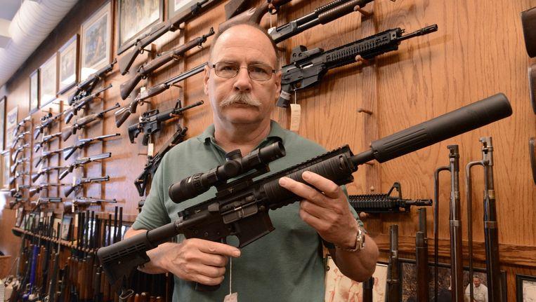 Een wapenverkoper in de Verenigde Staten toont een Colt AR-15-geweer. Beeld anp