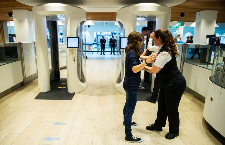 Een reiziger wordt  gefouilleerd door een beveiliger op Schiphol.   Beeld ANP