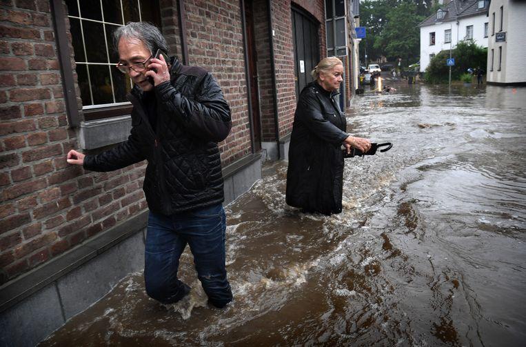 Water stroomt door de straten in Mechelen. Beeld Marcel van den Bergh / de Volkskrant