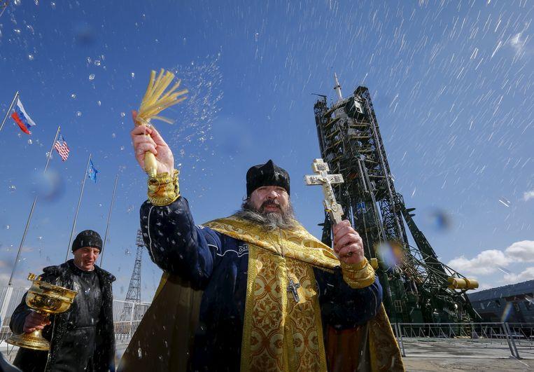 Een Russisch-orthodoxe priester zegent een raket op de lanceerbasis van Baikonoer in Kazachstan. Beeld REUTERS