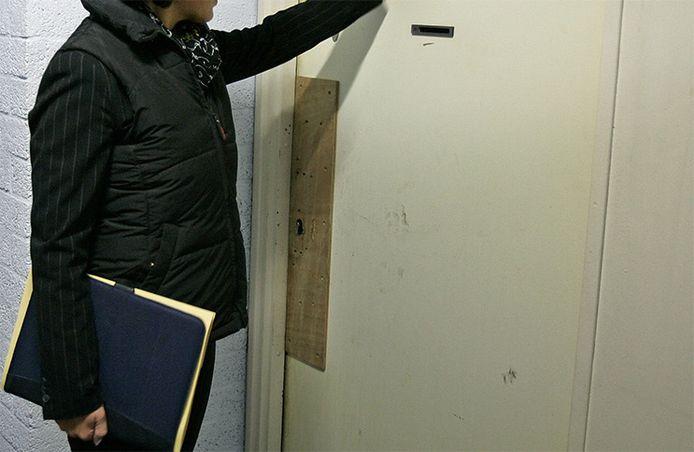 Foto ter illustratie. Een deurwaarder klopt op de deur