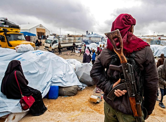 Een Koerdische beveiliger kijkt toe met een geweer op z'n rug hoe families hun spullen inladen om uit het kamp te vertrekken.