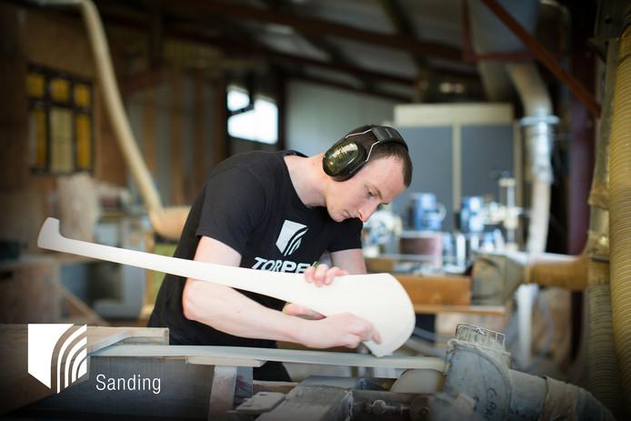 Een medewerker van hurleystickfabriek Torpey in Ierland aan de slag met een stick.