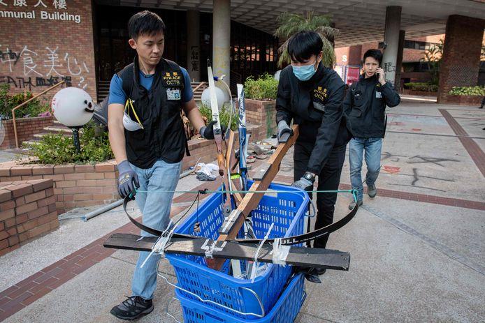 Politie-agenten duwen een mand met bogen naar buiten uit de campus van de Polytechnische universiteit waar pro-democratische demonstranten zich verschansten.