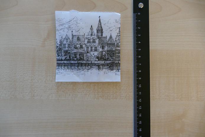 De afperser verstuurt de explosieve lading van de bombrieven in kleine papieren zakjes met een aanzicht van Delft.