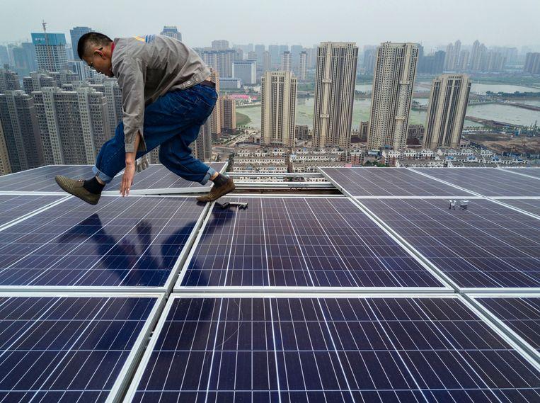 Een Chinese werkman legt zonnepanelen aan in de stad Wuhan. Beeld Getty Images