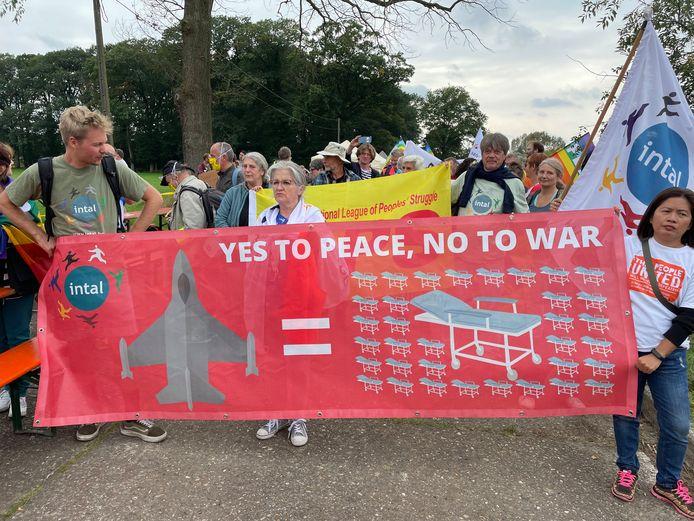 """De groep trok gewapend met spandoeken met slogans als """"Geen nieuwe kernwapens in Belgie"""" en """"Yes to peace, no to war"""" naar de oude toegangspoort van de luchtmachtbasis."""
