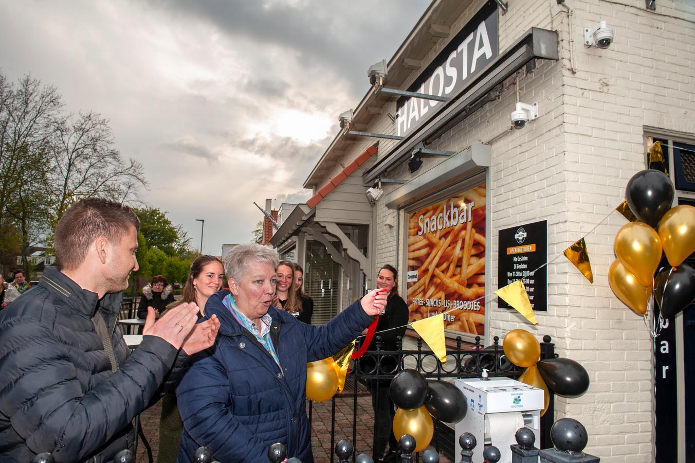 Go van Zanten heeft zojuist het lintje doorgeknipt van cafetaria Halosta in Aalst.  De nieuwe eigenaar Ashwin Swart (links) applaudisseert.