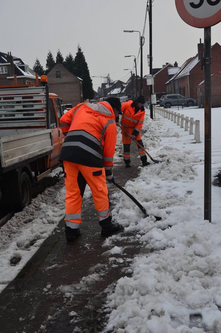 Gemeentearbeiders maken met de schop de voetpaden vrij.