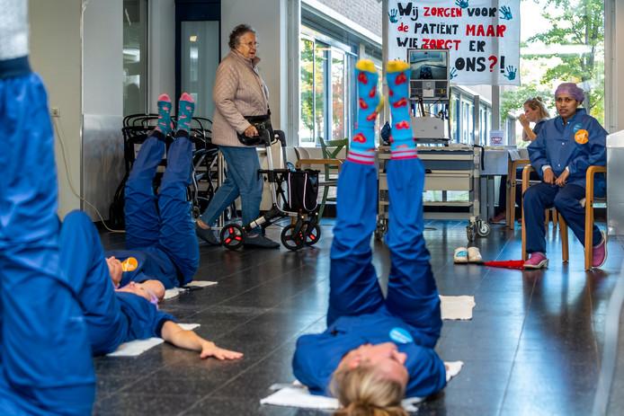 Personeel van het St. Antonius Ziekenhuis doet yogaoefeningen in de hal van het ziekenhuis.