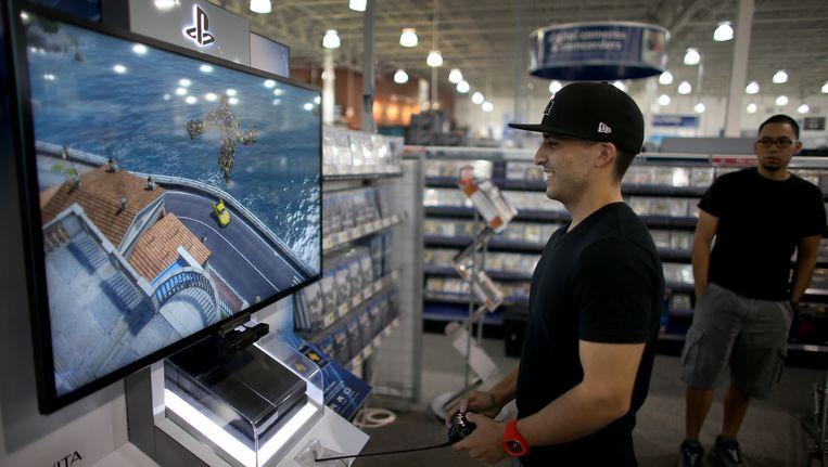 Een klant in een Best Buy-filiaal in Florida speelt met de nieuwe Playstation. Beeld GETTY