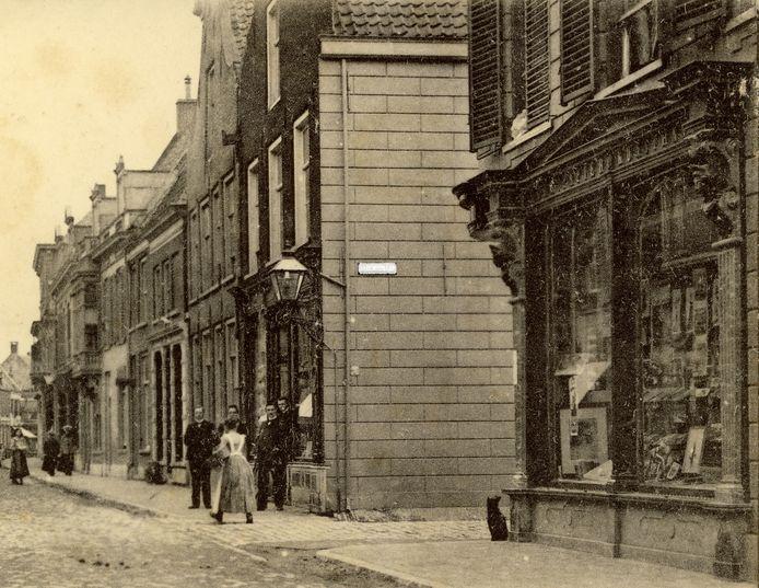 Een historische foto van de hoek van de Nieuwstraat met de Hoogstraat in Wageningen waarop nog een oud straatnaambord te zien is.