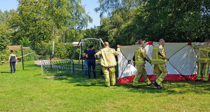 Hulpverleners plaatsen een scherm in de speeltuin waar een man om het leven is gekomen. Het slachtoffer overleed aan de gevolgen van een mishandeling.