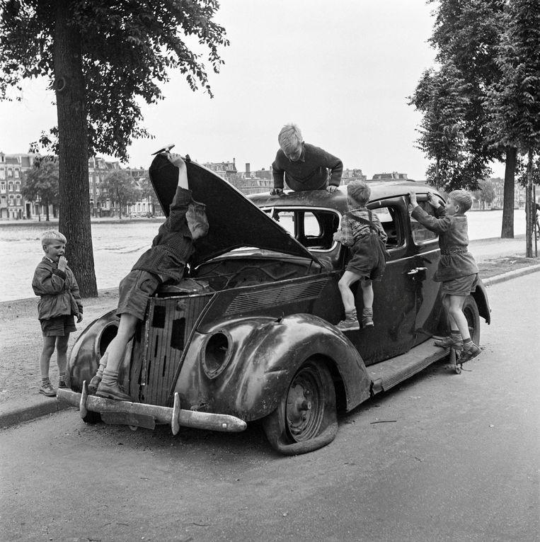 Jongetjes klimmen in 1954 op een sloopauto langs de weg in Amsterdam. Beeld Nederlands Fotomuseum /HH