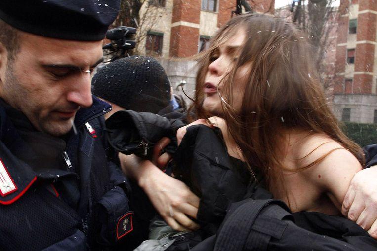 Drie vrouwen, volgens Italiaanse media lid van de actiegroep Femen, ontblootten bij de stembusgang van Silvio Berlusconi hun bovenlijf. Daarop stond de leus 'Basta Silvio!' ('Klaar met Silvio'). Beeld ap