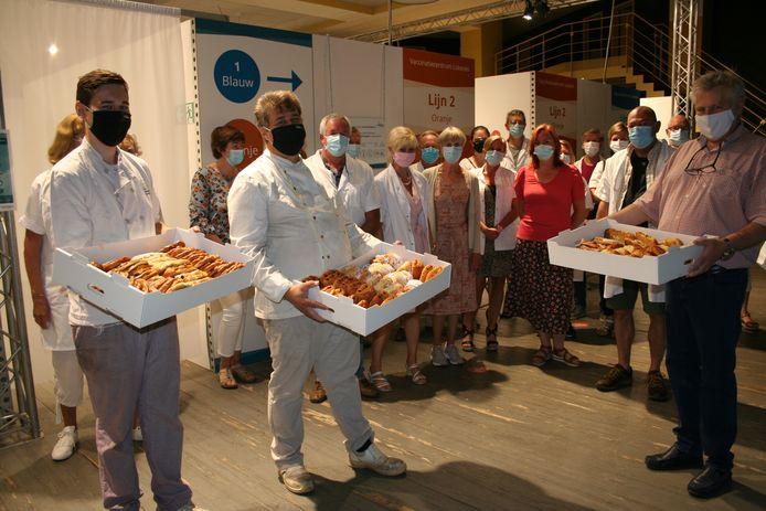Kenneth en Eddy Van Damme schenken de boterkoeken aan de medewerkers van het vaccinatiecentrum