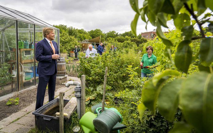Koning Willem-Alexander in gesprek met vrijwilligers tijdens een werkbezoek aan Gilde Stadstuiniers Zoetermeer in de Hof van Seghwaert.