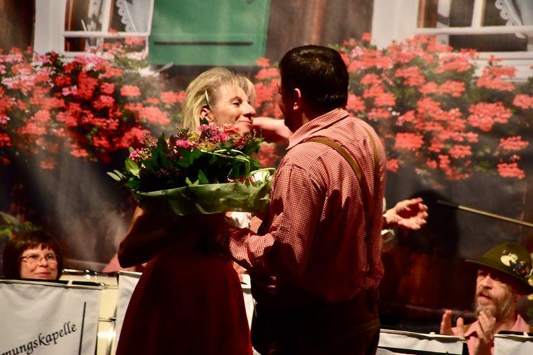 Katharina Eloot, de echtgenote van Marc Debruyne, geeft na afloop van het Heimatkonzert een ruiker bloemen aan Jacky Demuynck, die haar man heeft opgevolgd als dirigent van Die Original Dorfmusikanten.