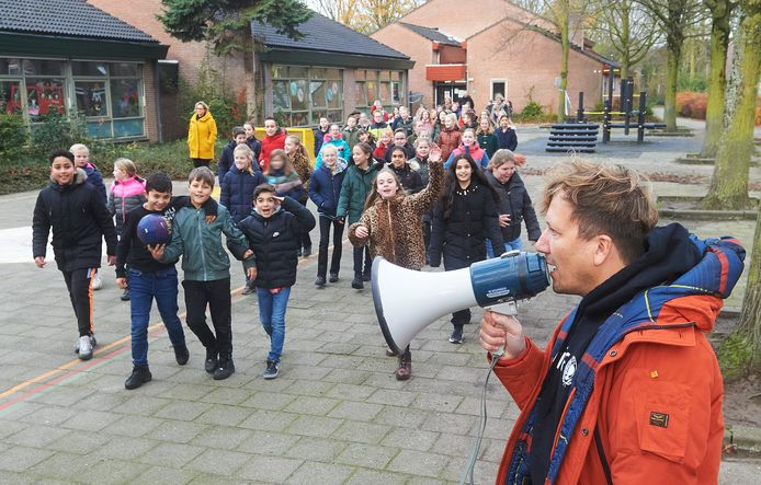 Presentator Klaas van Kruistum begeleidt de kinderen van groep 7 naar binnen voor de les over kinderrechten.