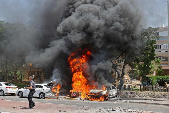 Brandende wagens in Ashkelon na een raketaanval vanuit Gaza.