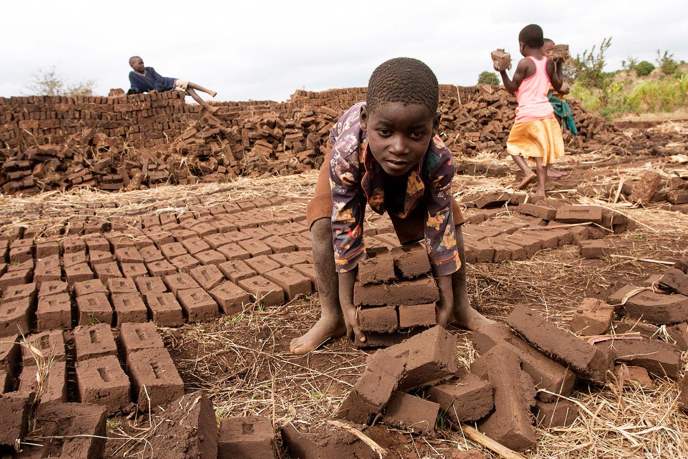 Een jongen in Malawi tilt bakstenen die gebakken moeten worden.
