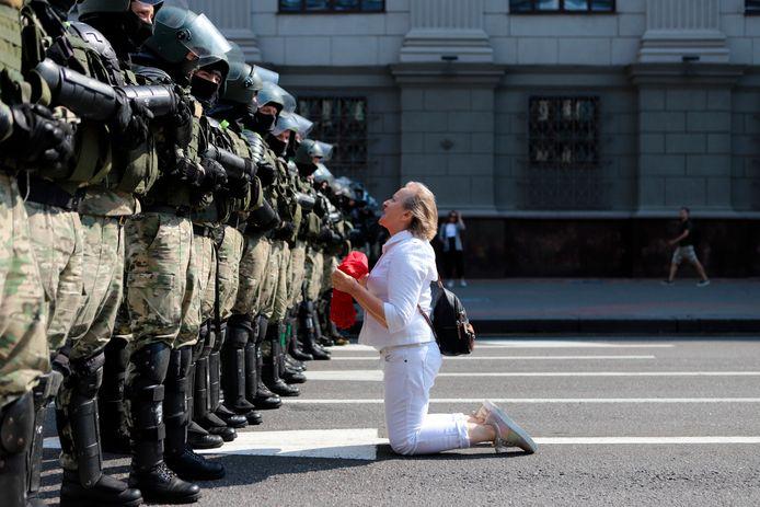 Een vrouw knielt voor de oproerpolitie in Minsk.