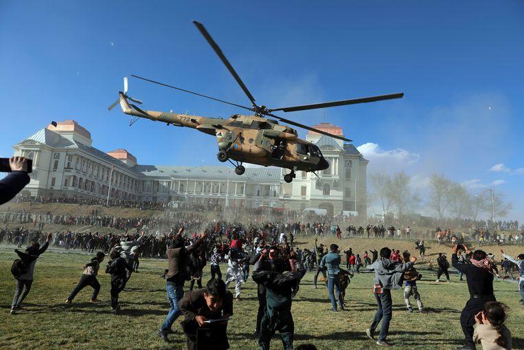 Dit lijkt een heftig tafereel, zeker omdat het zich in het Afghaanse Kaboel voordoet, maar deze helikopter maakt alleen een showduik voor de menigte die is afgekomen op de 'open dag' van de veiligheidstroepen. Daarop wordt het nieuwe materieel getoond.  Beeld AP