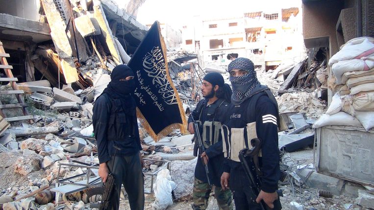 Leden van Al Nusra staan voor door de terreurgroep vernielde gebouwen. Beeld AFP