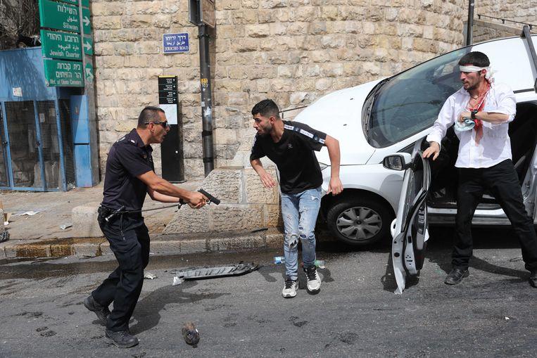 Een Israëlische politieman heeft zijn pistool gepakt. In het midden een Palestijn, rechts een  orthodox-Joodse autobestuurder. Jeruzalem op 10 mei 2021. Beeld EPA