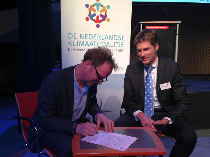 Gedeputeerde Johan van den Hout tekent de code van de Nederlandse Klimaatcoalitie.