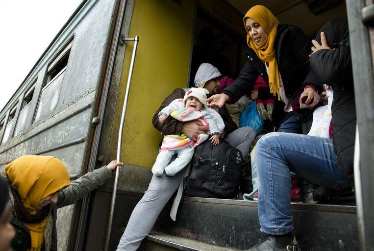 Vluchtelingen die net de grens van Griekenland en Macedonië gepasseerd hebben stappen op de trein naar Servië. Beeld anp