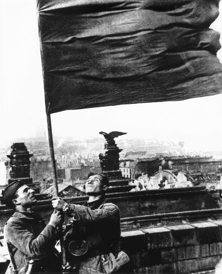 Soldaten van het Rode Leger hijsen op 2 mei 1945 de Sovjetvlag boven de Rijksdag in Berlijn. Beeld AFP