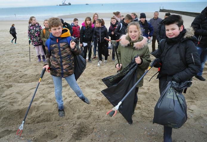 Scholieren verzamelen troep op het strand bij Dishoek. Op de voorgrond vlnr Tobias ter Velde, Mendy Boone en Dinand Scheermeijer.
