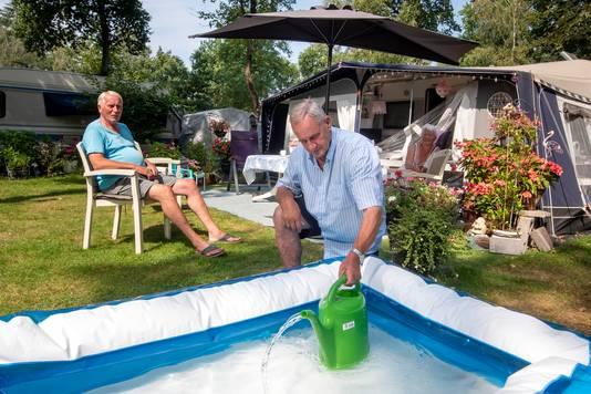 Ruud Beutick haalt wat water voor zijn planten uit het zwembad.