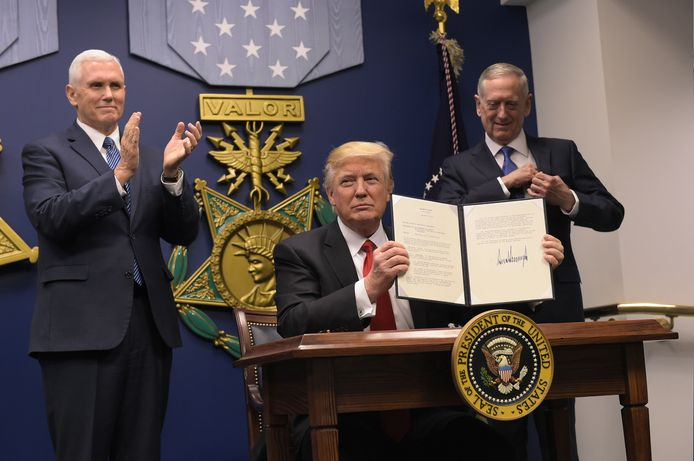 Donald Trump laat de ondertekende decreten zien in het Pentagon.