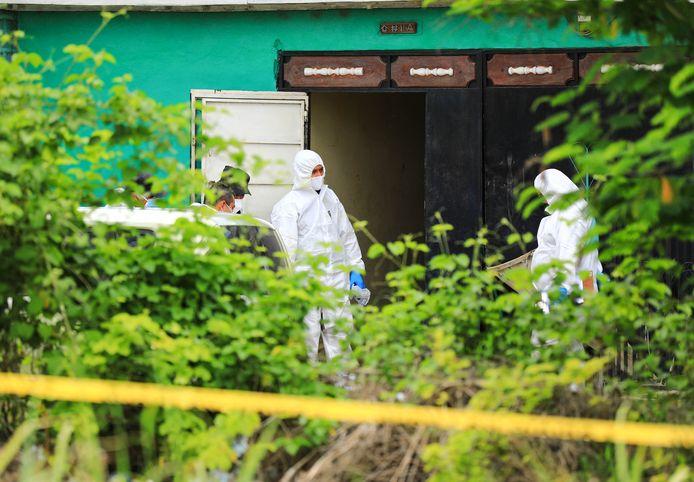 De politie ontdekte bij een inval de lichamen van twee vrouwen in een plas bloed, in de tuin werden daarna de lichamen van nog eens tien personen gevonden.