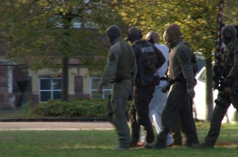 De 27-jarige dader wordt onder politiebegeleiding weggebracht naar het gerechtsgebouw van Karlsruhe. Beeld AFP